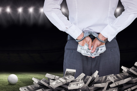 restraining device: Businessman in handcuffs holding bribe against football pitch at night with ball and lights