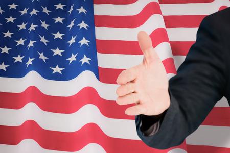 extending: Businessman extending arm for handshake against rippled us flag