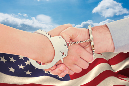 restraining device: Handcuffed business people shaking hands against blue sky Stock Photo