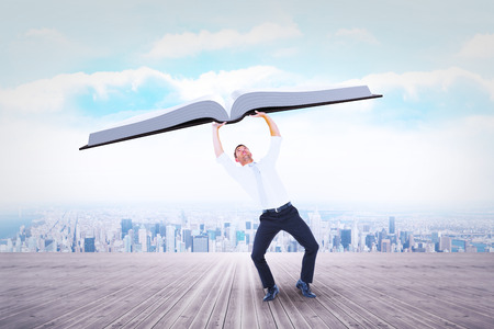 Businessman bending and pushing against city on the horizon Stock Photo