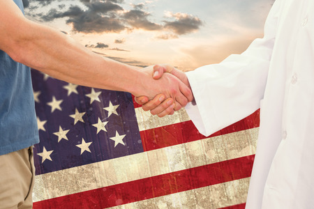 national flag: Mid section of a doctor and patient shaking hands against blue and orange sky with clouds Stock Photo