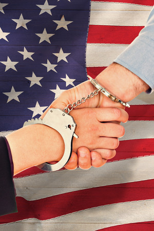 restraining device: Business people in handcuffs shaking hands against pale grey wooden planks
