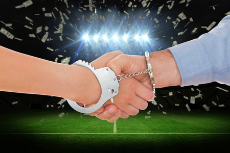 handcuffed hands: Handcuffed business people shaking hands against football pitch under spotlights