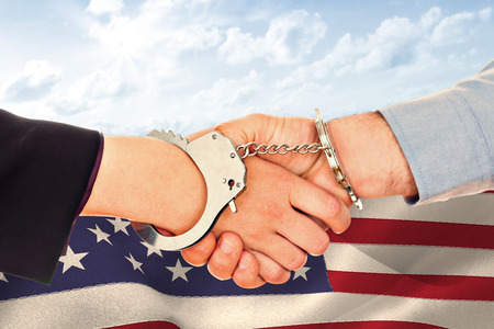 restraining device: Business people in handcuffs shaking hands against blue sky Stock Photo