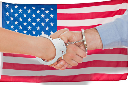 restraining device: Handcuffed business people shaking hands against grey