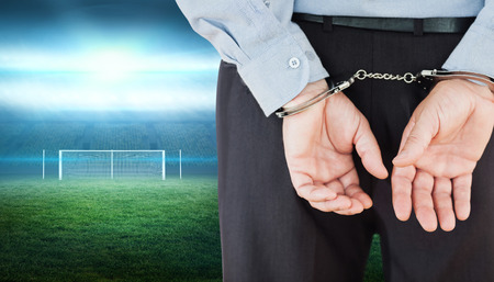 formals: Businessman in formals with handcuffs against football pitch with lights and goalpost Stock Photo