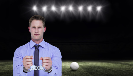 restraining device: Handsome businessman wearing handcuffs against football pitch at night with ball and lights Stock Photo