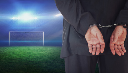 Businessman in handcuffs against football pitch with bright lights Stock Photo