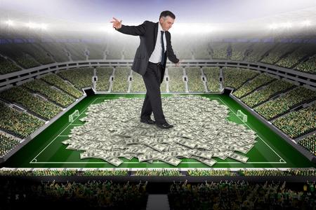 balancing act: Mature businessman doing a balancing act against pile of dollars