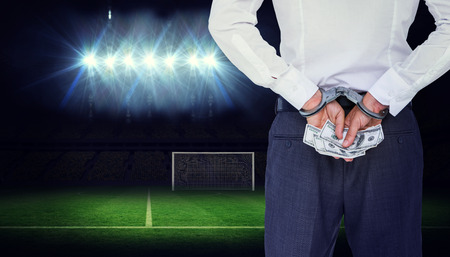 restraining device: Businessman in handcuffs holding bribe against football pitch under spotlights