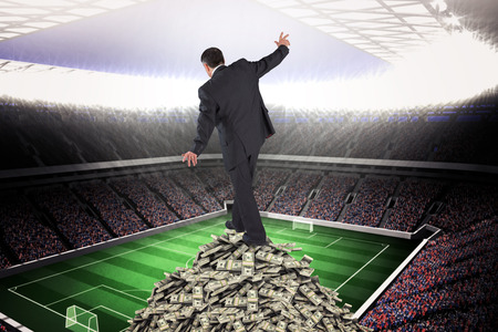 balancing act: Mature businessman doing a balancing act against large football stadium with lights Stock Photo
