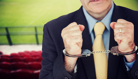 handcuffed hands: Closeup of businessman with handcuffed hands against red bleachers looking down on football pitch