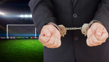 football pitch: Handcuffed businessman against football pitch with lights and flags Stock Photo