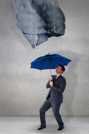 sheltering: Businessman sheltering under blue umbrella against grey room Stock Photo