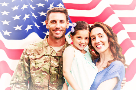 Soldier reunited with family against rippled us flag Reklamní fotografie - 42361072