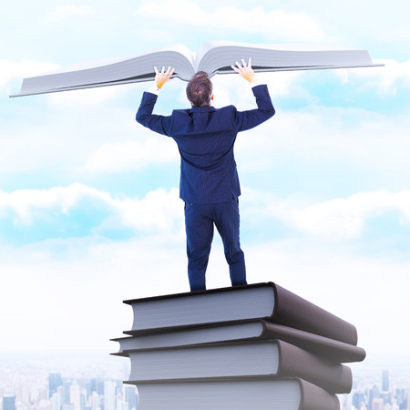 arms out: Businessman climbing on a cube with arms out against city on the horizon Stock Photo