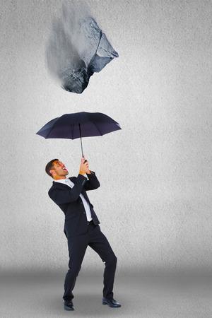 sheltering: Businessman sheltering under black umbrella against grey wall