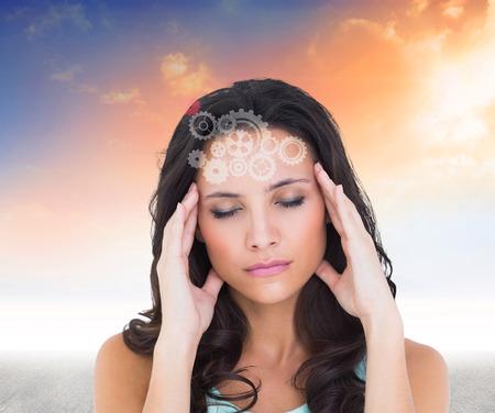 dolor de cabeza: Brunette bonito con un dolor de cabeza contra el cielo azul y naranja Foto de archivo