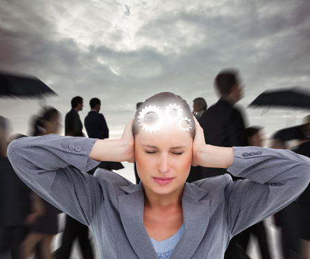 tradeswoman: Close up of annoyed tradeswoman covering her ears against grey sky Stock Photo