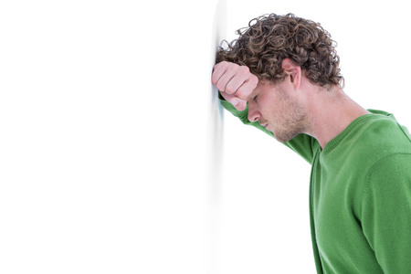 unhappiness: Sad casual man leaning against wall on white background
