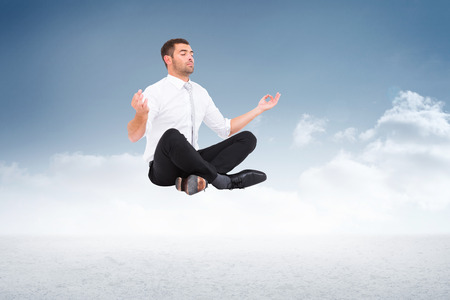 lotus pose: Businessman meditating in lotus pose against cloudy sky background Stock Photo