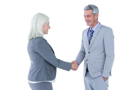 personas saludandose: El hombre de negocios dando la mano a una mujer de negocios contra una pared blanca