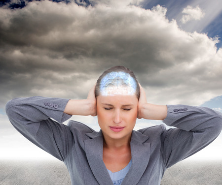 tradeswoman: Close up of annoyed tradeswoman covering her ears against cloudy sky