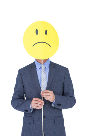 sad smiley: a young businessman holding sad smiley faced balloon on white background