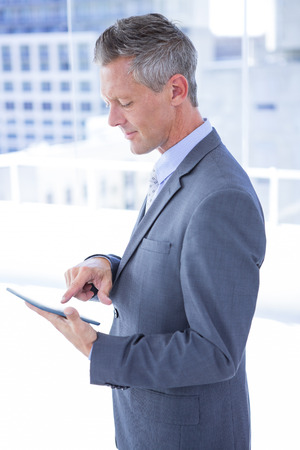 grey hair: Businessman holding a tablet in the office