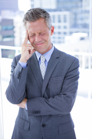 man hair: Businessman having a headache in the office Stock Photo