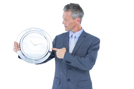 late 40s: Businessman holding and showing a clock on white background
