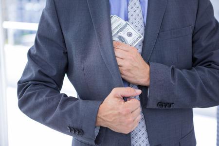 dodgy: Dodgy businessman pocketing a bundle of dollar bills