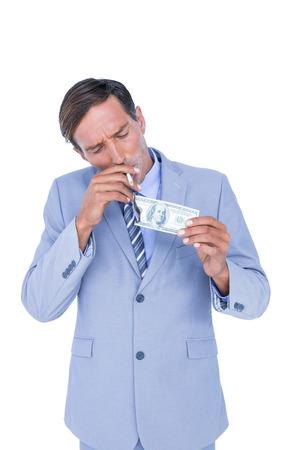 burning money: businessman burning a dollar banknote on white background