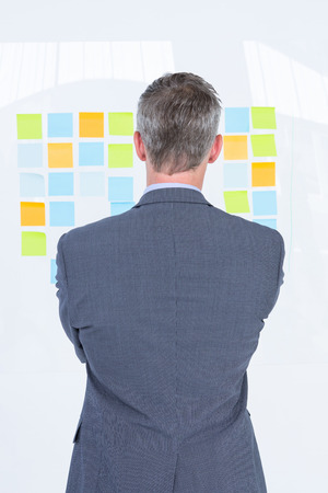inquiring: Puzzled businessman looking notes on the wall in the office