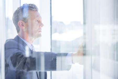 Pensare imprenditore in ufficio guardando attraverso la finestra