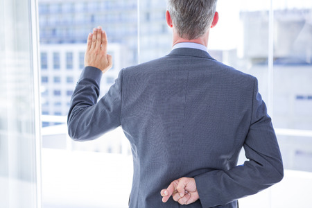 an oath: Businessman making a oath while crossing fingers behind his back