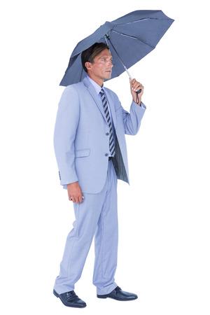 sheltering: Businessman sheltering under umbrella on white background