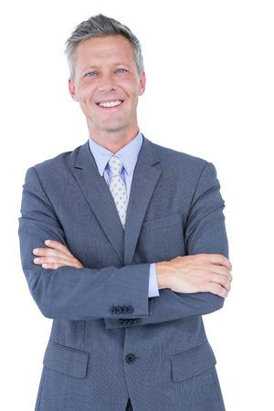 hombres maduros: hombre de negocios sonriendo con los brazos cruzados sobre un fondo blanco Foto de archivo