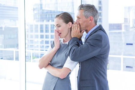 swish: Secretive business colleagues whispering in the office Stock Photo