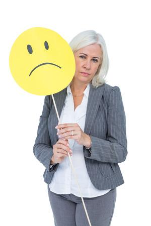 sad smiley: Businesswoman holding sad smiley face on white background