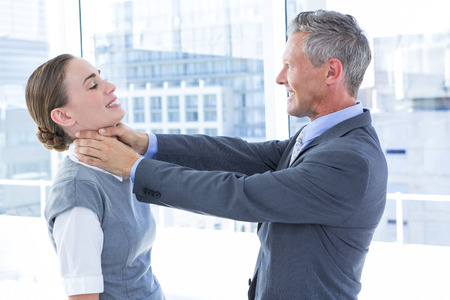 quell: Businessman trying to smother his colleague in the office Stock Photo