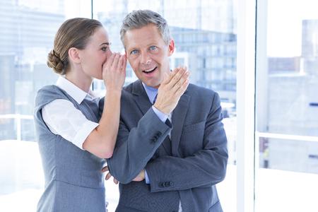 chismes: Colegas de negocios secretos susurran en la oficina Foto de archivo