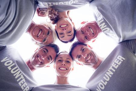 Gelukkig vrijwilliger familie naar beneden te kijken naar de camera op een zonnige dag