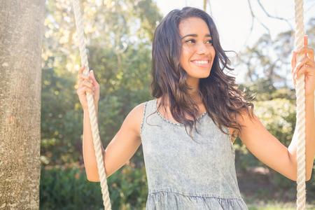 femmes souriantes: Jolie brune balancement dans le parc sur une journ�e ensoleill�e Banque d'images