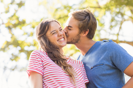 Cute couple kissing in the park on a sunny day