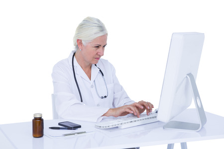 doctor computer: Doctor working on her computer on a white screen