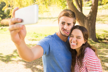 handsome guy: Cute couple doing selfie in the park on a sunny day Stock Photo