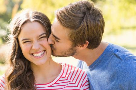 Casal bonito beijando no parque em um dia ensolarado Imagens