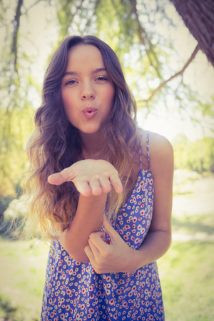 young  brunette: Pretty brunette blowing kiss at camera on a sunny day