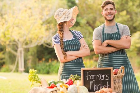 agricultor: Agricultores felices de pie brazos cruzados en un día soleado